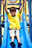 Junges intelligentes Kind, das hinunter das Schwingen schiebt lizenzfreie stockfotografie
