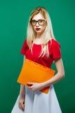 Junges intelligentes Mädchen in den Brillen mit Ordner von Dokumenten in den Händen steht auf grünem Hintergrund im Studio Ausbil Stockbild