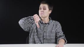 Junges interessantes Mädchen zeigt Missbilligungsseufzer, Daumen unten, schwarzer Hintergrund stock video