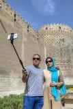Junges iranisches Paar macht Foto unter Verwendung des Selbststockes und des smartpho Lizenzfreies Stockfoto