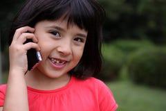 Junges Japanisch-Russisches Mädchen, das am Telefon lacht Lizenzfreie Stockfotos
