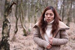 Junges japanisches Mädchengefühl am Unbehagen in einem Wald stockbild