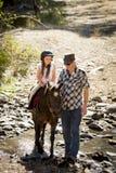 Junges Jockeykinderreitpony draußen glücklich mit Vaterrolle als Pferdelehrer im Cowboyblick Stockbild