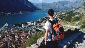 Junges jugendlich bewundert die Ansicht während des Aufstiegs zur Festung in Kotor in Montenegro Männlicher Brunette im weißen T- Lizenzfreies Stockfoto