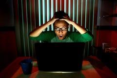 Junges jugendlich mit den Brillen, die vor einer Laptop-Computer überrascht fungieren Lizenzfreie Stockbilder