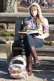 Junges Jugendlichmädchen, das auf einer Bank mit Buch sitzt Stockbild