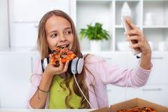 Junges Jugendlichmädchen, das Pizza in der Küche - Herstellung eines selfi isst Stockbilder