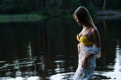 Junges Jugendlichmädchen im weißen Kleid und gelben im Badeanzug, die im Wasser steht Lizenzfreie Stockfotografie