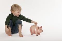 Junges Jungen-Einsparung-Geld in einer Münzen-Querneigung stockfotografie