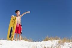 Junges Jungen-Kind auf einem Strand mit dem Surfbrett-Zeigen Lizenzfreie Stockbilder