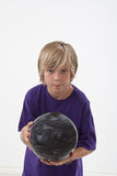 Junges Jungenbowlingspiel Stockfoto