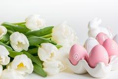 Junges Küken in Wanne, 2 malte Eier und Blumen Weiße Tulpen, bunte Eier auf Weiß lizenzfreie stockfotos