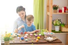 Junges Küken in Wanne, 2 malte Eier und Blumen Glückliche Mutter und ihr nettes Kind, die zu Ostern durch das Malen der Eier fert lizenzfreies stockfoto