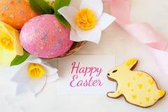 Junges Küken in Wanne, 2 malte Eier und Blumen Lebkuchen und Korb mit Eiern lizenzfreies stockfoto