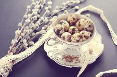 Junges Küken in Wanne, 2 malte Eier und Blumen Schwarzer Hintergrund Stockfoto