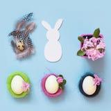 Junges Küken in Wanne, 2 malte Eier und Blumen Weißes Häschen und gemalte Hühnereien mit Blumendekor auf Blau Beschneidungspfad e Stockbilder