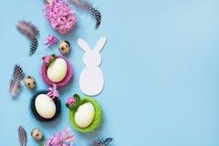 Junges Küken in Wanne, 2 malte Eier und Blumen Weißes Häschen und gemalte Hühnereien mit Blumendekor auf Blau Beschneidungspfad e Lizenzfreie Stockbilder