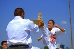 Junges Karatemädchen, das ein Brett bricht Stockfotos