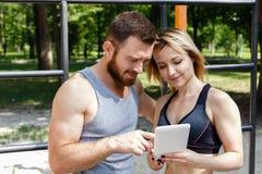 Junges kaukasisches blondes Mädchen und bärtiger Mann, die den Internierten grast Lizenzfreie Stockfotografie