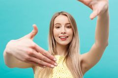 Junges kaukasisches Frauengesicht der Nahaufnahme und Augenpflege und sie, die Rahmen mit den Händen lokalisiert über blauem Past Lizenzfreie Stockfotografie