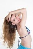 Junges kaukasisches Mädchen, das in swimsuitand Händen auf Haar aufwirft Stockfotos