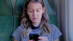 Junges kaukasisches Mädchen mit den schönen roten Nägeln, die in einem Flugzeug-, Zug- oder Busstuhl sitzen Benutzt einen mobilen stock video footage