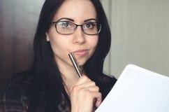 Junges kaukasisches Mädchen mit Gläsern verwahrt einen Stift und ein Dokument und denkt stockfotografie