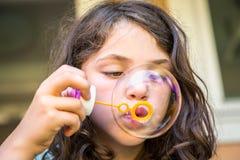 Junges kaukasisches Mädchenkinderschlagseifenblasen Stockfoto