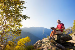Junges kaukasisches Mannsitzen im Freien auf einem Felsen, der an einem lapto arbeitet Stockbilder