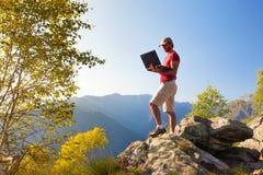Junges kaukasisches Mannsitzen im Freien auf einem Felsen, der an einem lapto arbeitet Stockfotografie