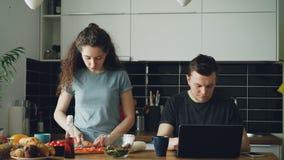 Junges kaukasisches Paar bei Tisch, Mann arbeitet an Laptop, ist er konzentriert und pencive, kocht Frau Ausschnitt stock video footage