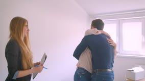 Junges kaukasisches Paar erhält Schlüssel von ihrer neuen Wohnung von der Immobilienagentur, die aufgeregt werden küsst und umarm stock video footage