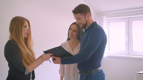 Junges kaukasisches Paar unterzeichnet Dokumente mit Immobilienagentur und Blicke um ihre neue Wohnung, die aufgeregt wird stock footage