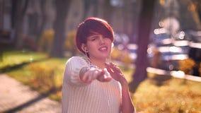 Junges kaukasisches rosa-haariges Mädchen mit Kopfhörern hörend Musik und auf sonnigen Parkhintergrund aktiv tanzend stockbild