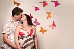 Junges kaukasisches schwangeres Paarküssen Stockfotos