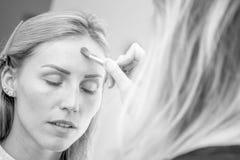 Junges kaukasisches weibliches Modell an einem Make-up Das Zutreffen bilden zu a Stockbild