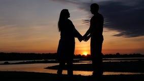 Junges Kerl- und Mädchenhändchenhalten, gegen einen schönen Sonnenuntergang und einen Fluss HD, 1920x1080 Langsame Bewegung stock video footage