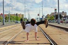 Junges Kerltanzen breakdance auf tramlines in der Stadt Stockfoto