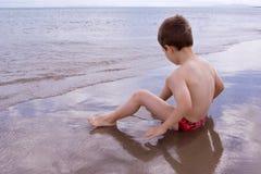 Junges Kind alleine auf dem Strand Lizenzfreie Stockbilder