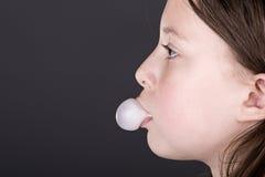 Junges Kind, das eine Luftblase mit Gummi durchbrennt Lizenzfreie Stockbilder
