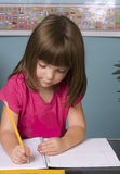 Junges Kind, das an ihrem Schreibtisch im Klassenzimmer arbeitet lizenzfreie stockfotos