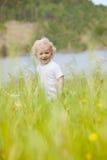 Junges Kind im hohen Gras Lizenzfreies Stockfoto