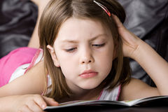 Junges Kind-Messwert ihr Buch auf dem Sofa Lizenzfreies Stockbild