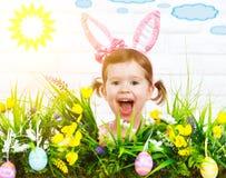 Junges Küken in Wanne, 2 malte Eier und Blumen Glückliches lustiges Kindermädchen im Kostümhäschen mit GR Lizenzfreie Stockfotos