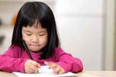 Junges kleines asiatisches Mädchen, das lernt zu schreiben lizenzfreies stockfoto
