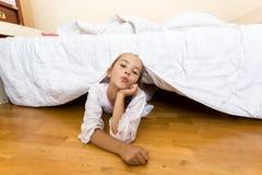 Junges kleines Mädchen, das auf Boden am Schlafzimmer unter Bett liegt stockbilder