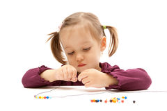Junges kleines Mädchen, das auf weißem Hintergrund bördelt Stockbild