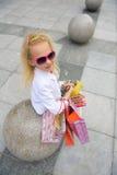 Junges kleines Mädchen mit vollen Einkaufstaschen Lizenzfreies Stockbild