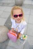Junges kleines Mädchen mit vollen Einkaufstaschen Stockfoto