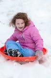 Junges kleines Mädchen, welches das Rodeln draußen an einem Schneetag genießt Stockfotos